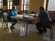 Voter Carolina Kauff listens to Election Clerk Dennis Plane explain how to fill out a provisional ballot.
