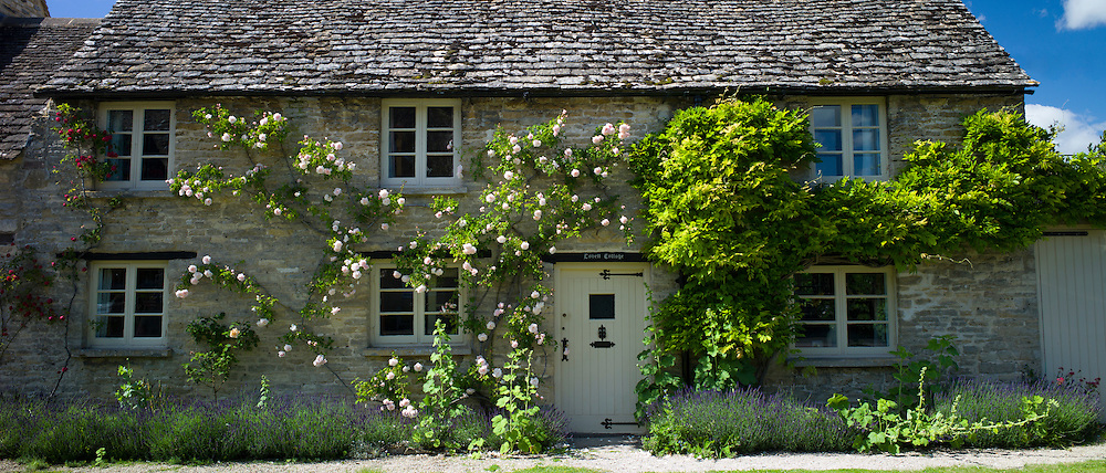 Quaint traditional rose-covered cottage in Minster Lovell in The Cotswolds, Oxfordshire, UK