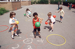 Junior school children playing with coloured balls in playground,