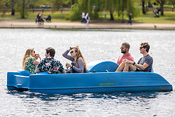 Licensed to London News Pictures. 09/05/2021. London, UK. Friends enjoy a bit of boating in the sunshine on the Serpentine in Hyde Park London, as the Met Office predict bbq weather today (Sunday) with temperatures hitting over 21c in London and the South East as the miserable May weather starts to warm up. Photo credit: Alex Lentati/LNP