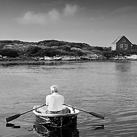 Sailor rows across Damariscove Harbor. Black and white portrait of a boater in dingy.