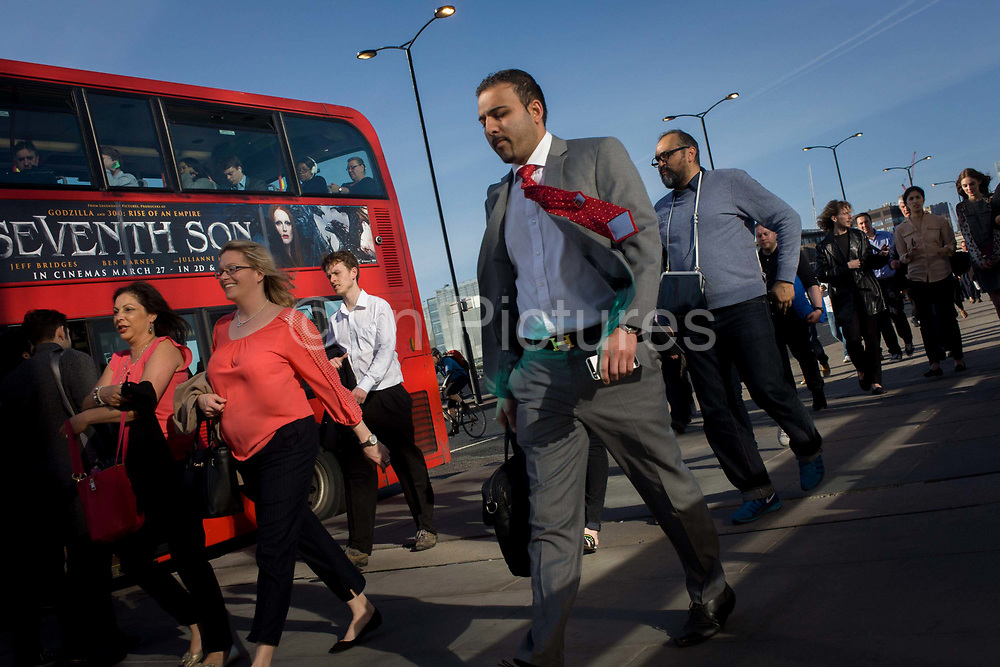Londoners cross southbound over London Bridge during the evening rush hour. Alongside a bus, a young man strides along with a with red tie flapping in the breeze to his ear, followed by others walking out of the City of London. There has been a crossing over the Thames here since the Romans first forded the river in the early 1st Century with subsequent medieval and Victorian stone bridges becoming an important thoroughfare from the City on the north bank, to Southwark on the south where transport hubs such as the mainline station gets commuters to the suburbs and satellite towns.