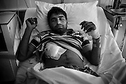Athens, Greece - Aftab Ali, 22, from Pakistan, lies in a bed in Kat Hospital after being repeatedly stabbed from a group of Golden Dawn activists. In Greece, the deep recession due to the Austerity Measures imposed by the Troika (European Union, European Central Bank, and International Monetary Fund) coincided with the worsening in life conditions of both the native population and the immigrant one. The latter had to face not only an enormous increase of poverty and unemployment -often leading to homelessness- but also the rise in popularity of Golden Dawn, an ultranationalist party which got 18 seats in Parliament after June 2012 election. G.D. propaganda and actions are all based on racism and hate towards the foreign communities, blamed to be one of the main causes of the crisis.<br /> Bruno Simões Castanheira