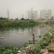 Kids come to look for floating garbages such as plastic bottles, plastic bags etc. They will make few rupees per day by giving it to a shop that send it to recycling plants. The Shahadra open air sewer in Noida, when it exits Delhi. Authorities have proclaimed the drainage waters too dirty to wash animals in it.