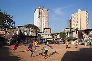 Young men play football on a red earth pitch with wooden favela buildings in the background. Opening World Cup 1014 game, Favela Do Moniho, Sao Paulo, Brazil.