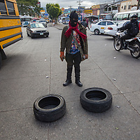 A lone masked protestor stands amid traffic with two tyres ready to burn them and stones in his hands.