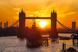 © Licensed to London News Pictures. 24/02/2016. London, UK. A bright orange sunrise behind Tower Bridge in central London on a cold winter morning.  Photo credit: Colin Hart/LNP