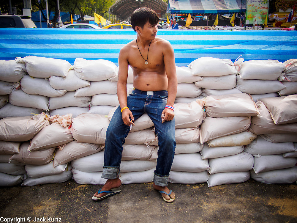 """30 DECEMBER 2013 - BANGKOK, THAILAND: An anti-government protestor rests on a pile of sandbags he helped place across Ratchadamnoen Road in Bangkok. Violence around the anti-government protest sites has escalated in recent days and several protestors have been hurt by small explosive devices thrown at their guard posts. As a result, protestors are fortifying their positions with sandbags and bunkers. Suthep Thaugsuban, the leader of the anti-government protests in Bangkok, has called for a new series of massive protests after the 1st of the year and said it the shutdown, or what he described was the seizure of the capital, would be the day when """"People's Revolution"""" would """"begin to end and uproot the Thaksin regime.""""          PHOTO BY JACK KURTZ"""