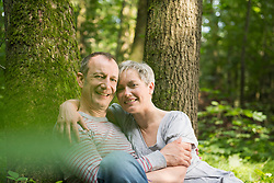 Portrait of mature couple sitting by tree in forest, smiling