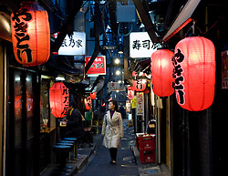 Narrow alleyway lined with small restaurants at night in Shinjuku Tokyo Japan