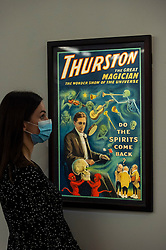 """© Licensed to London News Pictures. 24/09/2021. LONDON, UK. A staff member views a vintage poster of """"Thurston the Great Magician"""", printed c.1915, (Est $8,000-12,000). Preview of a collection spanning the history of magic from celebrity magician Ricky Jay.  The works are being shown in Sotheby's, New Bond Street, ahead of their auction in New York on 27 and 28 October.  Photo credit: Stephen Chung/LNP"""