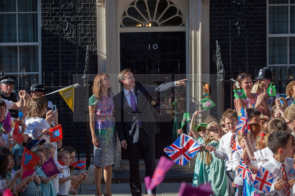 © licensed to London News Pictures. London, UK 26/07/2012. David Cameron points the torch as the torch relay comes to Downing Street. Photo credit: Tolga Akmen/LNP