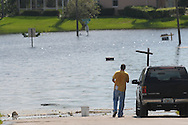 A man looks on from the water's edge on a neighborhood street flooded by the heavy rains of Tropical Storm Fay in Debary, Florida, Wednesday, Aug. 27, 2008.