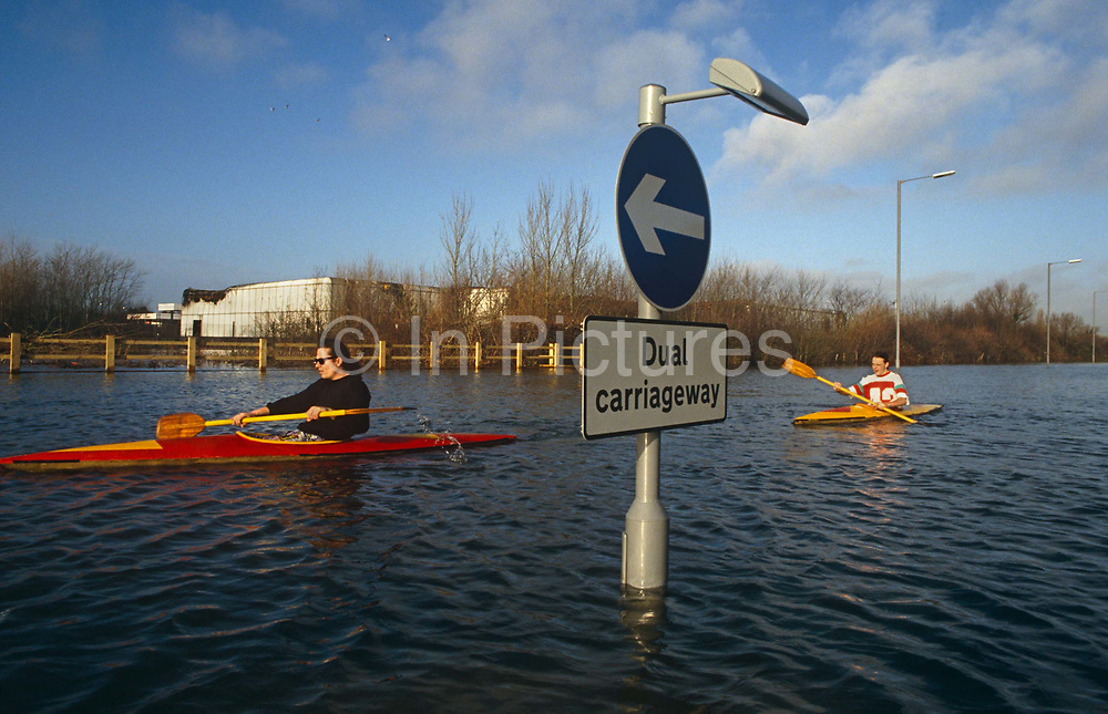 After heavy rain and the subsequent flooding, two lone canoeists paddle down the centre of the A27 near Chichester, West Sussex. The Dual carriageway has been completely submerged to approximately 1.5 metres and only the road sign with its directional arrow is visible above the surface which is rippling in a faint breeze. The men in red and yellow kayaks look inexperienced in boating activities and their clothing is not suitable for water sports. Even so, they are speeding down the highway that is otherwise empty of all other vehicles and they have the water and space to themselves without the fear of collision.