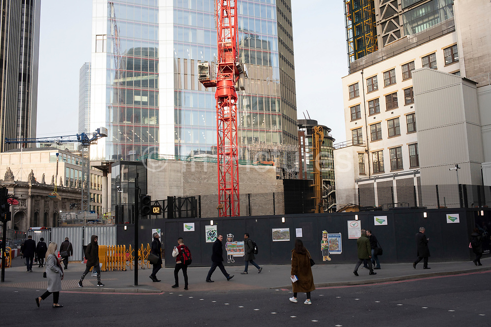 Street scene with people passing another construction site for the latest skyscraper in the City of London on 5th February 2020 in London, England, United Kingdom. The City of London is a city, county and a local government district that contains the historic centre and the primary central business district CBD of London.