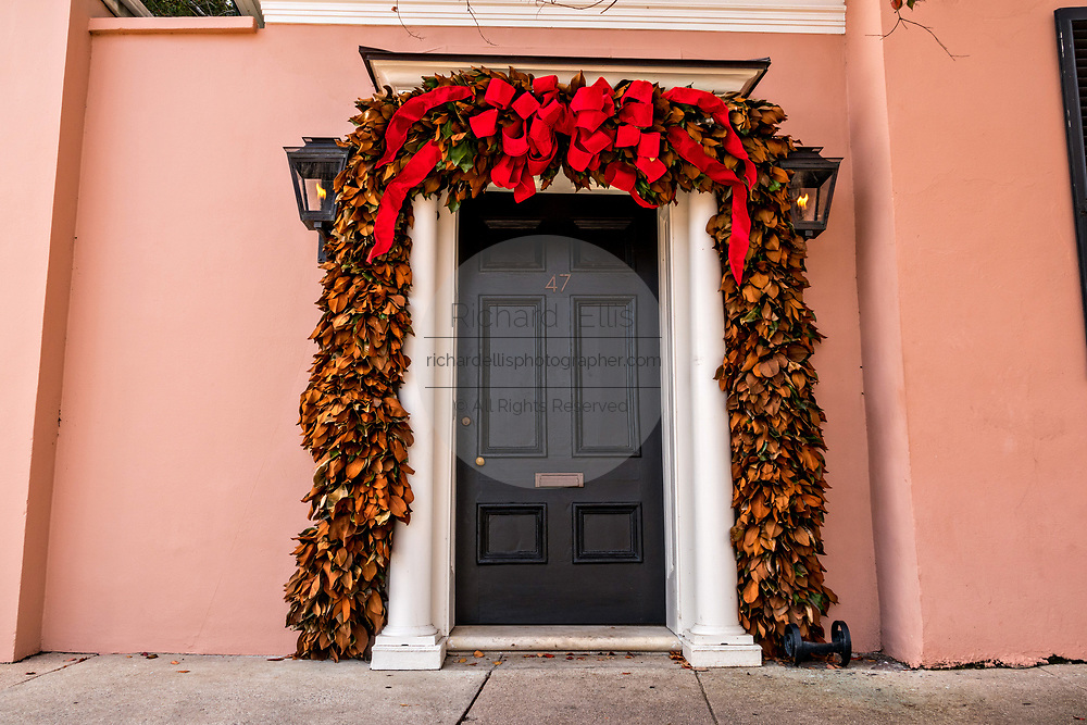 Magnolia Christmas roping and bows decorate the wooden door of a historic home on East Bay Street in Charleston, South Carolina.