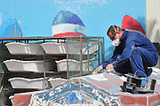 Israel, Eilat man fixing a fibreglass boat with protective clothes and mask