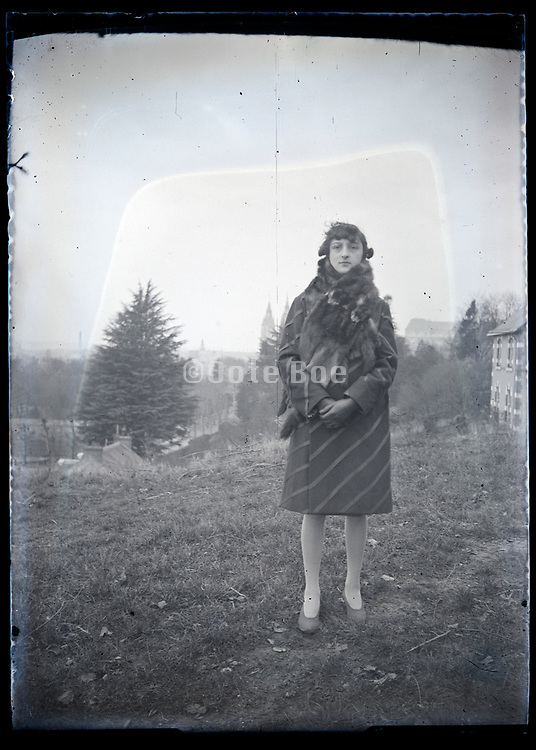 woman posing with a mountain village in the background France circa 1920s