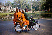 Three monks catch a ride on a motorcyle at Angkor Wat, Siem Reap, Cambodia. Four is not a crowd on a motorcycle in Southeast Asia.