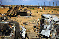 Local residents walk through a tank graveyard that used to be a staging post for pro-Ghaddafi forces poised to take Benghazi that was devastated by coalition forces enforcing the no-fly zone over eastern Libya