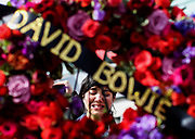 A fan cries at a makeshift memorial surrounds David Bowie's star on the Hollywood Walk of Fame in Los Angeles, Monday, Jan. 11, 2016. Bowie, the infinitely changeable, fiercely forward-looking songwriter who taught generations of musicians about the power of drama, images and personae, died Sunday surrounded by family. He was 69. Bowie died after an 18-month battle with cancer.