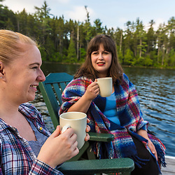 Two women drink coffee on the dock on Long Pond at the Appalachian Mountain Club's Gorman Chairback Lodge.