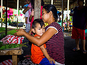 20 JANUARY 2018 - CAMALIG, ALBAY, PHILIPPINES: Edena Vargas sorts herbs for cooking with her son, MJ, at an evacuation shelter for people displaced by the eruption of Mayon volcano. More than 30,000 people have been evacuated from communities on the near the Mayon volcano in Albay province in the Philippines. Most of the evacuees are staying at school in communities outside of the evacuation zone.   PHOTO BY JACK KURTZ