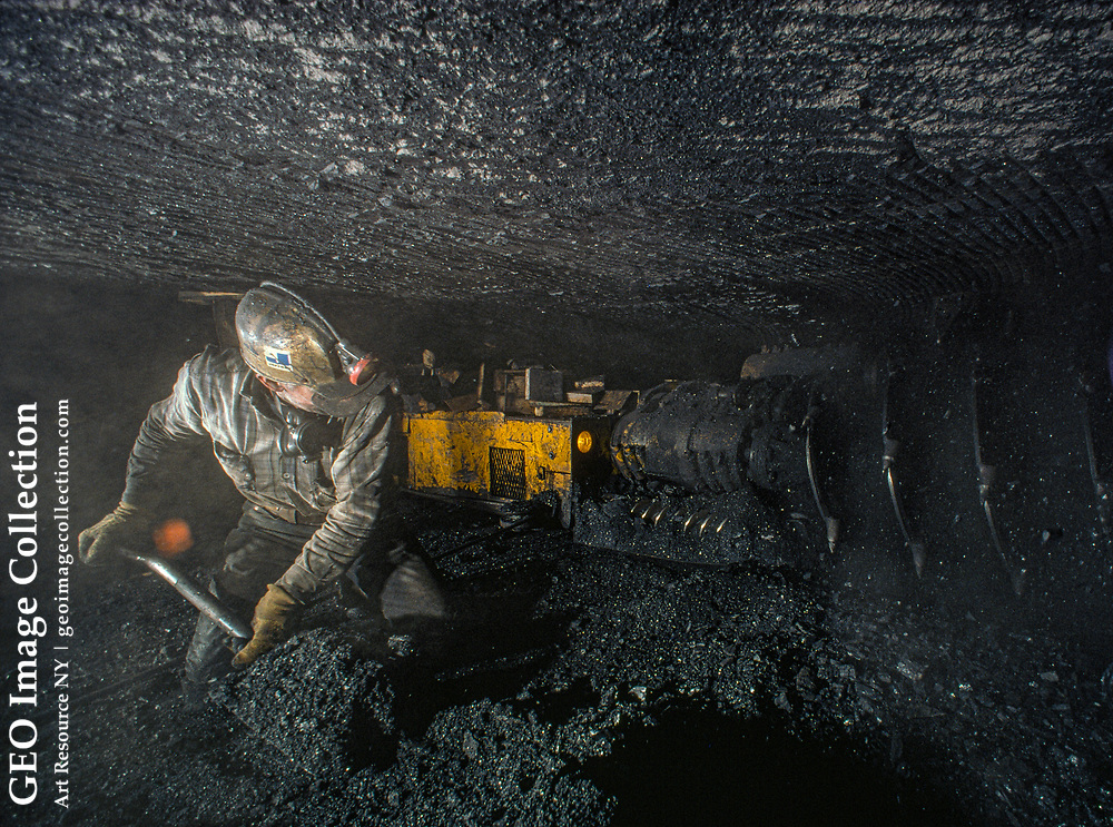 A miner shovels coal in a low seam of a mine.