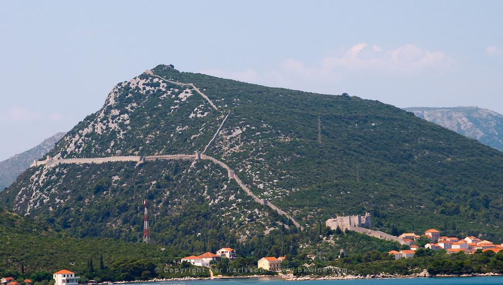 The Ston fortress built in the 14th century, and part of the 5 km long wall. View from the Mali Ston side Peljesac Peninsula. Ston. Peljesac peninsula. Dalmatian Coast, Croatia, Europe.