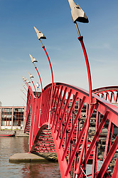 Modern red steel footbridge called Pythonbrug connecting Borneo and Sporenburg Island district of Amsterdam Netherlands