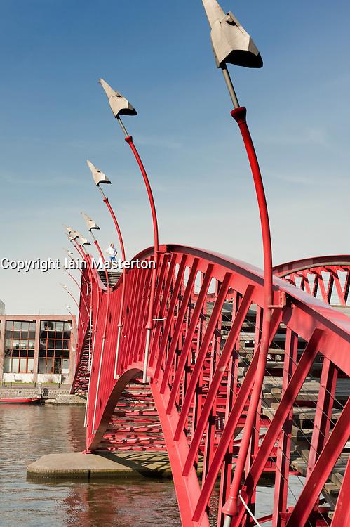 Modern red steel footbridge called Pythonbrug connecting Borneo and Sporenburg Island district of Amsterdam Netherlands