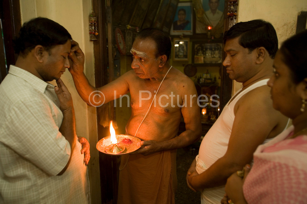 The family priest gives a blessing (puja) to Radakrishna and Srikanda Stpathy and their wives in the family shrine in the Stapathy house.The current Stpathy family is the twenty third generation of bronze casters dating back to the founding of the Chola Empire. The Stapathys had been sculptors of stone idols at the time of Rajaraja 1 (AD985-1014) but were called to Tanjore to learn bronze casting. Their methods using the ,?Úlost wax,?Ù process remains unchanged to this day..