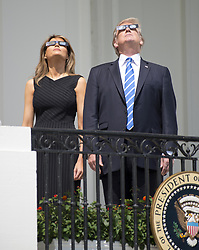 August 21, 2017 - Washington, District of Columbia, U.S. - United States President DONALD J. TRUMP, right, and First Lady MELANIA TRUMP look at the partial eclipse of the sun from the Blue Room Balcony of the White House. (Credit Image: © Ron Sachs/CNP via ZUMA Wire)