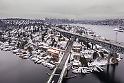Overhead view of Portage Bay in foreground and Lake Union in background, and a snow-covered Capitol Hill at left. Downtown Seattle is further in the background. (Steve Ringman / The Seattle Times)