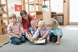 Female educator and four kids sitting on  ground of kindergarten looking at picture book