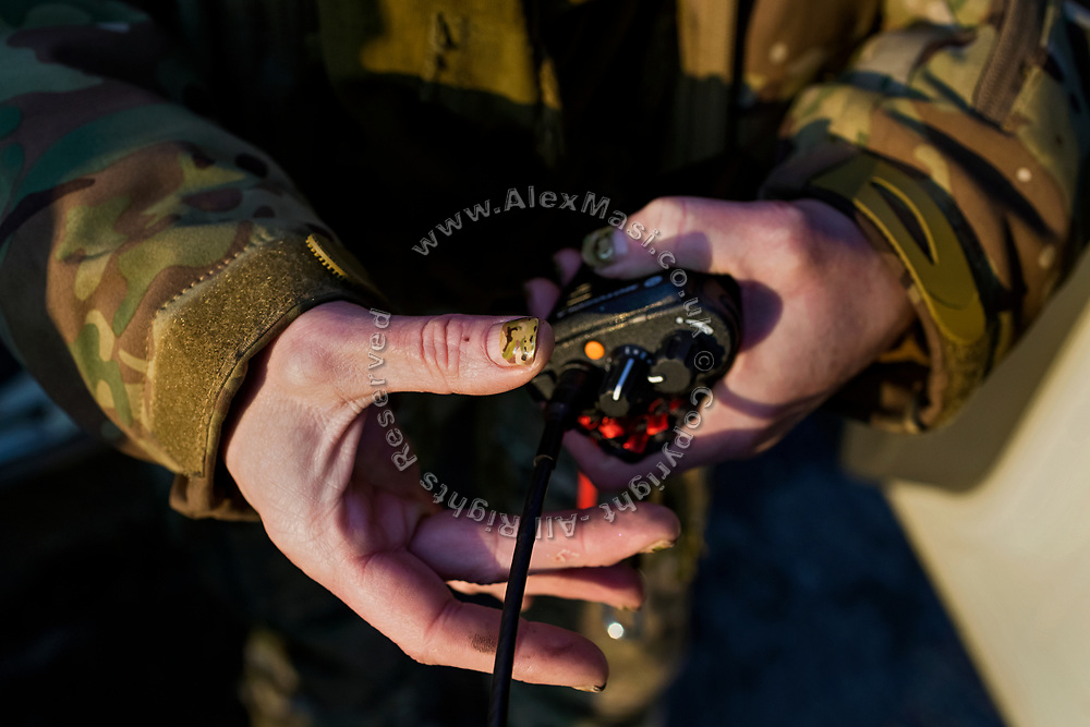 Julia Paevska is checking her radio while at the Mayorsk ASAP base near the frontline in eastern Ukraine.