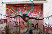 A young man walks past a mural, Street scene, San Cristobal de las Casas, Chiapas, Mexico.