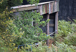 NOTE TO EDITORS : IMAGES SHOT FROM PUBLIC FOOTPATH © Licensed to London News Pictures. 11/08/2020. Bisley, UK. A barn is cordoned off as investigators search an area at Priest Lane Farm near Bisley in Surrey as part of an historic murder investigation. Surrey Police, supported by the British Army and specialist forensic teams are carrying out a dig in relation to the murder of Tina Baker, 41, in 2002. Tina was initially reported missing after last being seen in Sunbury on 8 July 2002 but the investigation became a murder enquiry in October 2002. In 2005, following an extensive investigation by the Surrey and Sussex Major Crime Team, Tina's husband, Martin Gerald Baker, was arrested and charged with her murder. In 2006, he was sentenced to 14 years behind bars. Tina's body was never recovered. Following the conviction, enquiries continued by Surrey Police in order to find out what happened to Tina Baker's body. Information received has resulted in the decision to carry out forensic investigations in Bisley. Photo credit: Peter Macdiarmid/LNP