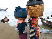 Arriving along the Ayeyarwady (Irrawaddy) river by small boat from their village, two women wearing thanaka (traditional Burmese sunscreen/moisturiser) carry bamboo baskets of vegetables on their heads for selling at the market in Bagan, Central Myanmar, Myanmar (Burma).