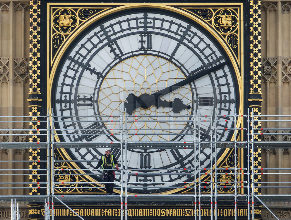 © Licensed to London News Pictures. 12/10/2017. London, UK. A scaffolder looks out from in front of a clock face on The Elizabeth Tower, known as Big Ben at Parliament. Scaffolding will reach a height of 96 meters when completed - the work is part of a three-year programme to conserve the Great Clock, the Elizabeth Tower and Big Ben. London, UK. Photo credit: Peter Macdiarmid/LNP