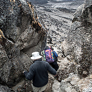 Hikers navigate the rugged terrain of the rocky apline desert on Mt Kilimanjaro Lemosho Route. These shots were taken on the trail between Moir Hut Camp and Lava Tower at approximately 14,500 feet.