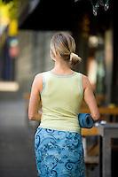 Young woman walking down sidewalk with yoga mat.