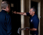 (L to R) Alan Bull and Raul Moreno of the Dallas Police Department go door to door as a part of the new 10/70/20 program at The Lodge at Timberglen apartments in Dallas on Saturday, March 30, 2013. (Cooper Neill/The Dallas Morning News)