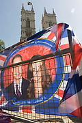 Days before their royal marriage in London, the faces of Prince William and his wife-to-be Kate Middleton, appear on flags attached to railings opposite the towers of Westminster Abbey. Their wedding takes place on Friday 30th April in front of millions of Btitons and foreign tourists. The faces of the couple are slightly obscured and twisted as the flag blows in a breeze in the capital. The royal standard is flying on the Abbey's left tower and crowds are already gathering at this prime location to see the ceremony occur across the road.