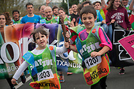 """Two children carry the baton as they run on the 20th Korrika.  Irun (Basque Country). April 4, 2017. The """"Korrika"""" is a relay course, with a wooden baton that passes from hand to hand without interruption, organised every two years in a bid to promote the basque language. The Korrika runs over 11 days and 10 nights, crossing many Basque villages and cities. This year was the 20th edition and run more than 2500 Kilometres. Some people consider it an honour to carry the baton with the symbol of the Basques, """"buying"""" kilometres to support Basque language teaching. (Gari Garaialde / Bostok Photo)"""