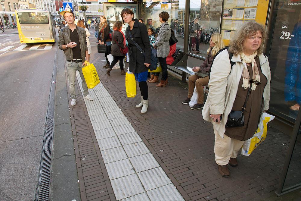 Met tassen vol van de Drie Dwaze Dagen van de Bijenkorf of de Zeeman wachten reizigers op de bus bij de Neude in Utrecht.<br /> <br /> With bags filled with stuff from the sale, people are waiting at the bus stop in Utrecht.