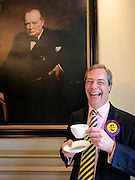 © Licensed to London News Pictures. 26/04/2012. London, UK . Nigel Farage MEP and leader of UKIP drinks from a cup  under a portrait of former Prime Minister Winston Churchill. The UK Independence Party (UKIP) local election campaign launch at St Stephen's Club, Central London. Photo credit : Stephen Simpson/LNP