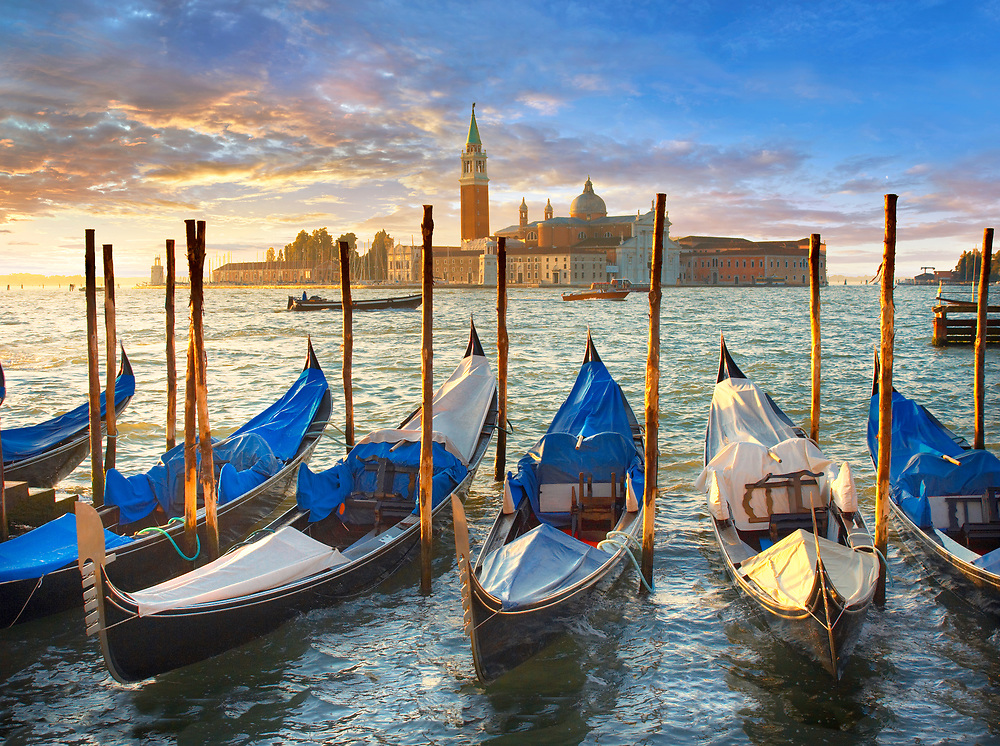 Sunset view of gondolas at St Mark's Square with the island of San Giorgio Maggiore behind , with its church front designed by Andrea Palladio and begun in 1566.  Venice Italy