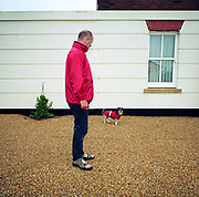 On its regular morning walk and wearing a matching red coat as its owner, a small dog exercises in Holmead Road in the experimental community village of Poundbury, Dorset, England. As the mutt looks at the camera, the man waits for him to stop sniffing around before moving on. The pair stand on crunchy gravel, a deterrent for would-be thieves who might be tempted to this small town where middle-class residents live. Poundbury is the visionary model village that Charles, Prince of Wales sought to develop in 1993 as a successful and pioneering town near Dorchester, built on land owned by his own Duchy of Cornwall, challenging otherwise poor post-war trends in town planning and to some extent following the New Urbanism concept from the US except that the design influences are European.