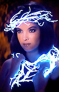 Portrait of a young woman with a glowing vine wrapped around her head and chest.Black light